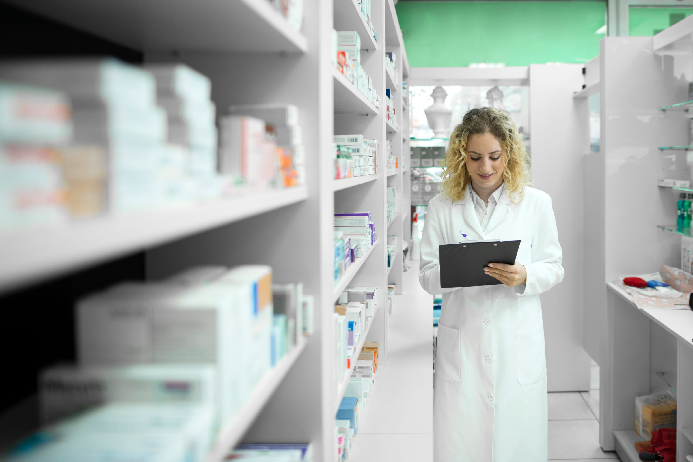 Pharmacist White Uniform Walking By Shelf With Medicines Checking Inventory