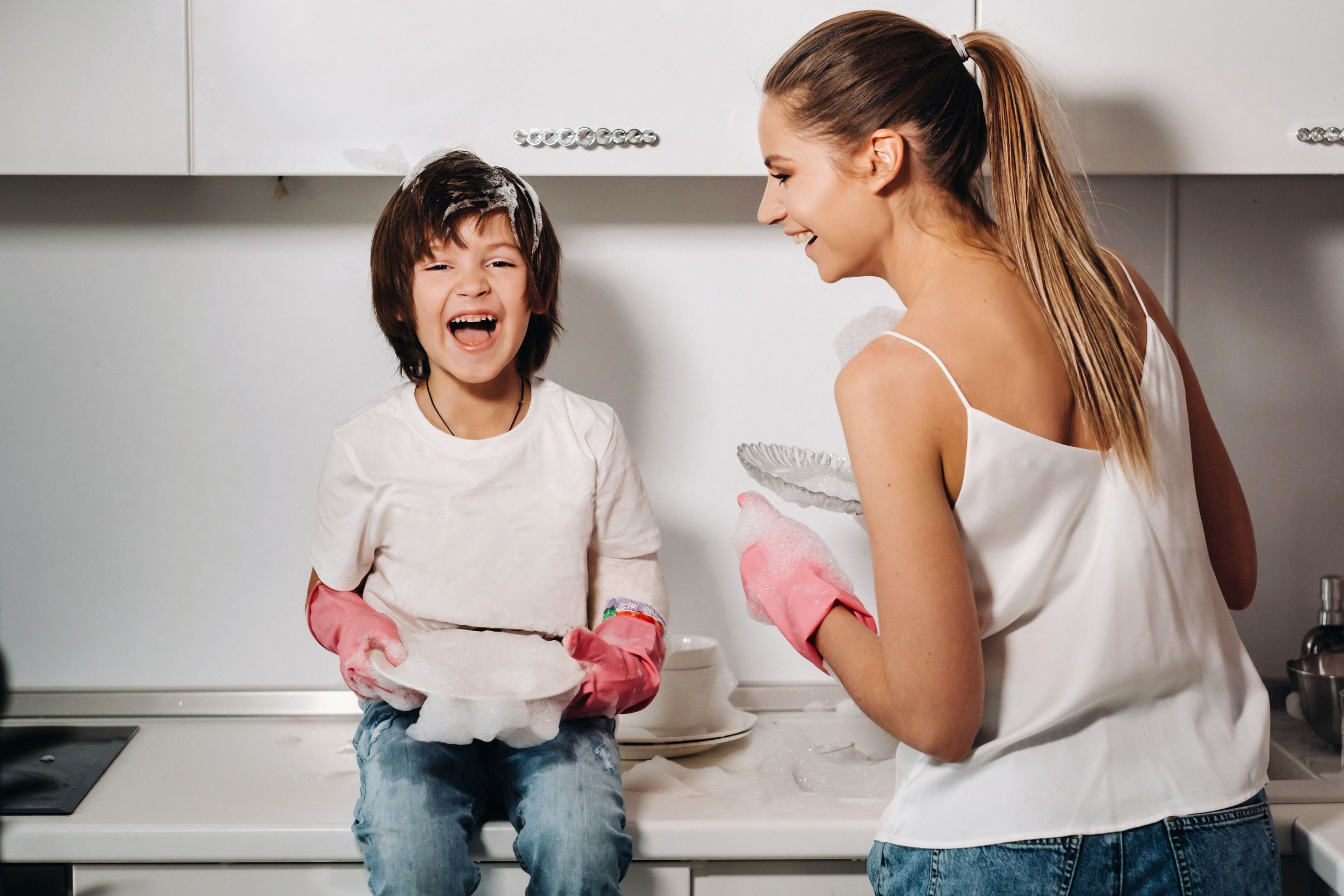 Housewife Mom Pink Gloves Washes Dishes With Her Son By Hand Sink With Detergent Girl White Child With Cast Cleans House Washes Dishes Homemade Pink Gloves (1)
